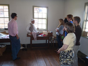 Students of HIS 5585: Historic Preservation listen to a tailor discuss his work at Old Salem, Single Brothers House.
