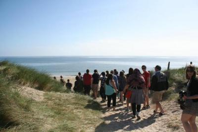 group of students walking toward a beach